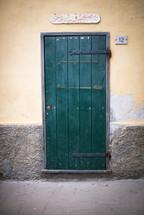 A green door in a stucco wall.