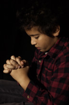 little boy with his fingers laced in prayer to God