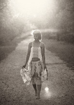 woman walking barefoot on a trail