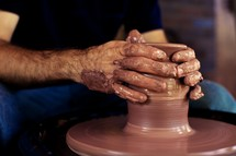 A potter molds clay on a potter's wheel