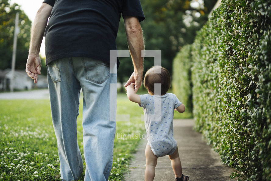 grandfather and toddler holding hands