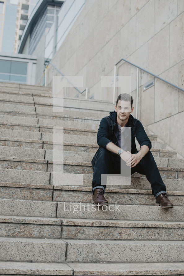 a man sitting on concrete steps