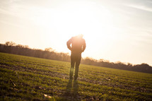 silhouette of a man in a field glowing under sunlight
