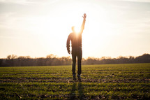 silhouette of a man jumping in a field with his hand raised to God glowing under sunlight