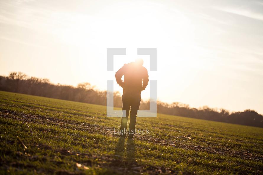 silhouette of a man in a field glowing under sunlight