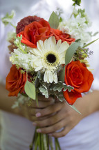 a bride holding a bouquet of red and white flowers