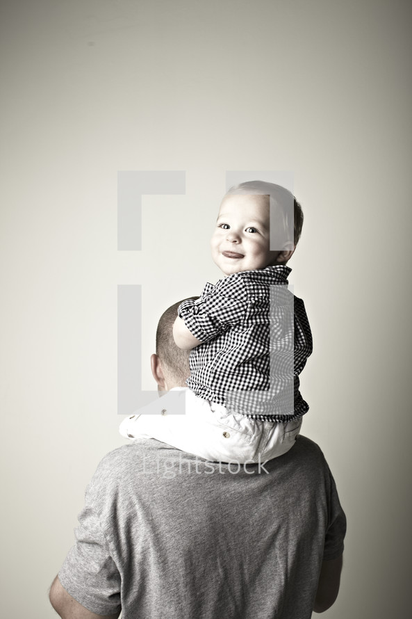 A young son sits on his father's shoulders