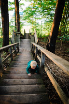 toddler boy on steps outdoors by a lake