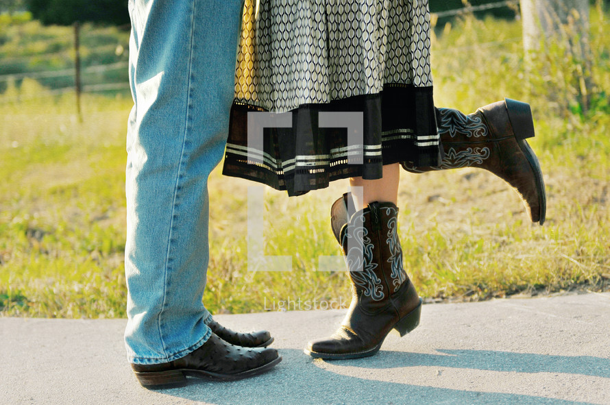The legs and feet of a man and woman in cowboy boots.