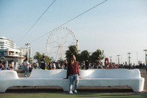 a woman sitting on a bench with a ferris wheel in the background