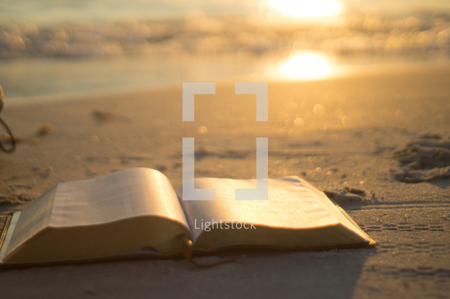 open Bible on a beach at sunrise
