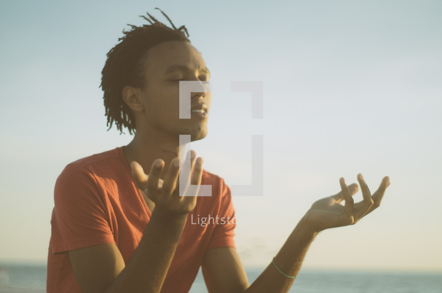 african-american man sitting on a beach meditating
