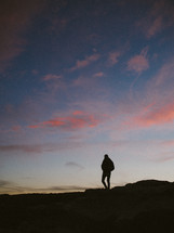 silhouette of a person walking on a mountaintop at sunset