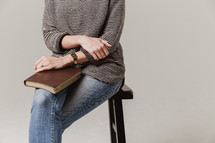 woman sitting on a stool with a Bible in her lap