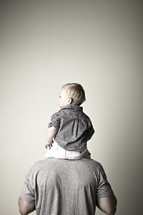 A toddler sits on dad's shoulders
