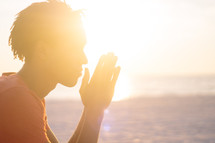 sunlight on a man's face and praying hands