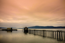 Pier leading to a boathouse in the water with mountains on the horizon at dusk.