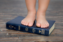 a child standing on a Bible - foundation in God