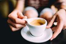 A woman sits with a cup of coffee in a white coffee cup.