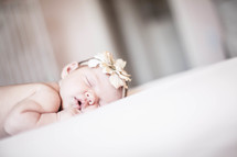 Infant with headband sleeping on tummy in crib.