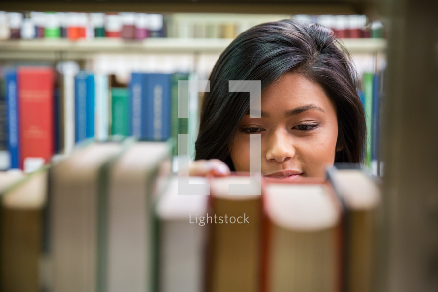 girl looking at books on a bookshelf in a library.