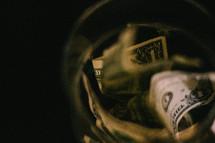dollar bills in a glass jar