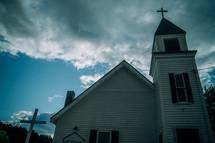 a rural white church with a steeple