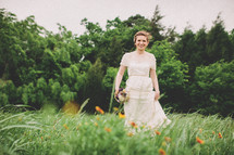 Bride with flower bouquet in field