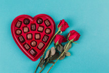 A heart shaped box of chocolates and three red roses.