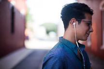 man walking in an alley listening to an iPod