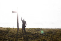 a man praying in front of a cross with a raised hand