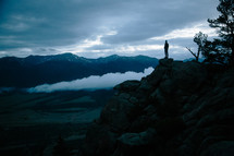 a man standing at the edge of a cliff at dusk