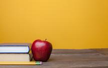 apple, books, and pencil on a teacher's desk