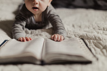 infant's hands on the pages of a Bible