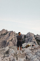a man with camping gear standing along on a rocky mountaintop