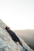 a man leaning against the side of a mountain resting