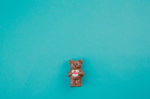 "A chocolate bear holding a heart that says ""be mine"" on an aqua background."