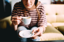 A woman on a coach drinking coffee from a white coffee cup.