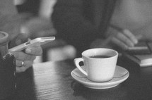 coffee cup on a table and looking at a cellphone screen