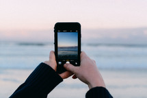 Taking a picture of the ocean with a cell phone.