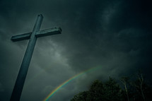 a cross in a gray sky and a rainbow