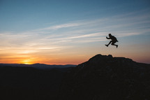 silhouette of a leaping man at sunset on a mountaintop