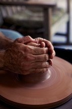 A potter molding clay into a pot