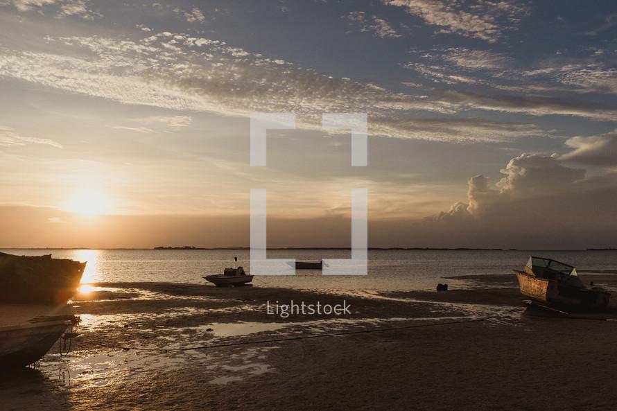 boats along a shore in the Bahamas at sunset