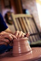 Potter molding clay into pot