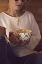 a young woman holding a tea cup