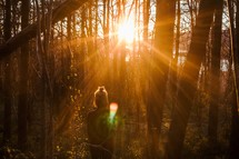 a woman standing in a forest under a sunburst