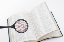 A magnifying glass over a Bible, magnifying John 3:16.