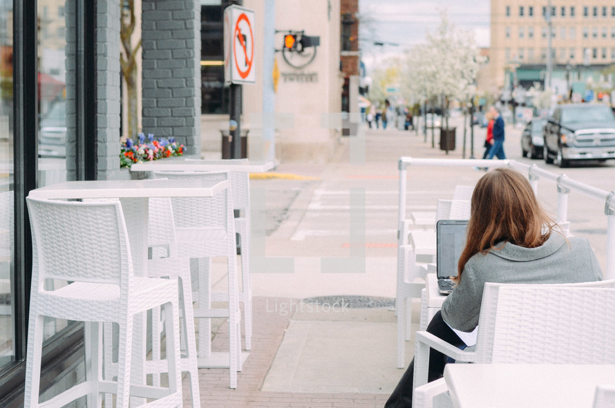 a woman typing on a computer sitting outdoors