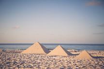 building pyramid sand castles on a beach